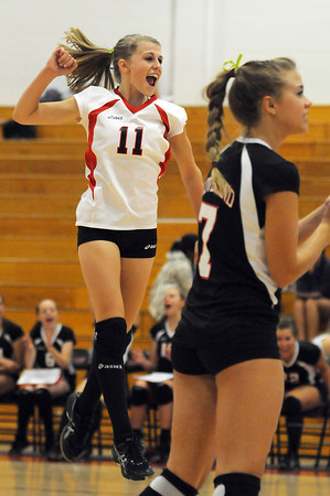 Loveland High School junior Stephanie Hutsell, left, and senior Kendahl Holley celebrate a point during the second game of Wednesday night's match at Loveland High School.