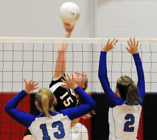 Loveland High School junior Andrea Alles slams a ball toward Thornton High School senior Katie Young, left, and junior Kyra Aragon during the first game of Wednesday night's match at Loveland High School.