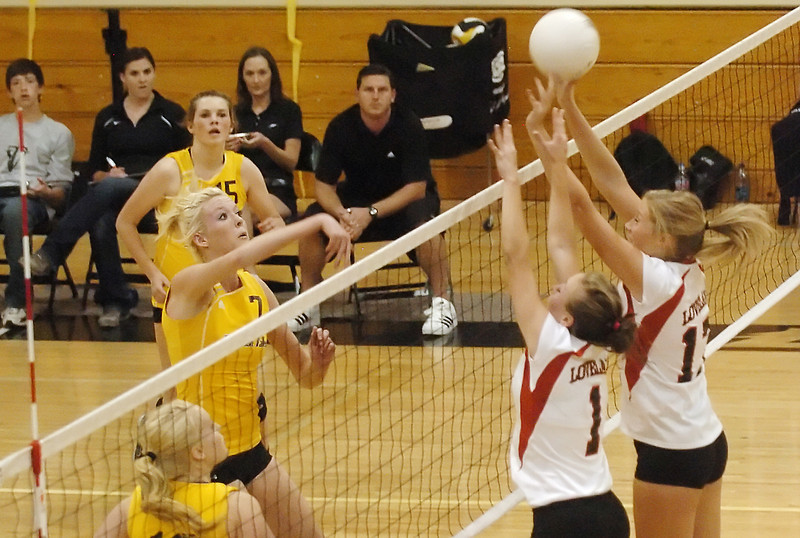 Thompson Valley High School senior Erin Marolf (7) attemps a spike past Loveland's Alyssa Steine (1) and Katie Dotson (17) while Meghan Miller (15) and Ciara Krening, bottom left, look during game two of their match Friday, Oct. 8, 2010 at TVHS. The Eagles won, 3-0.