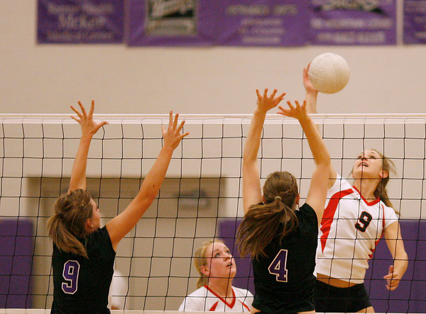 Loveland High School senior, Devyn Mueller, spike the ball on Mountain View's Bri Dupre, 9, and Holly Brouwer Monday at Mountain Valley High School. Photo by Gabriel Christus