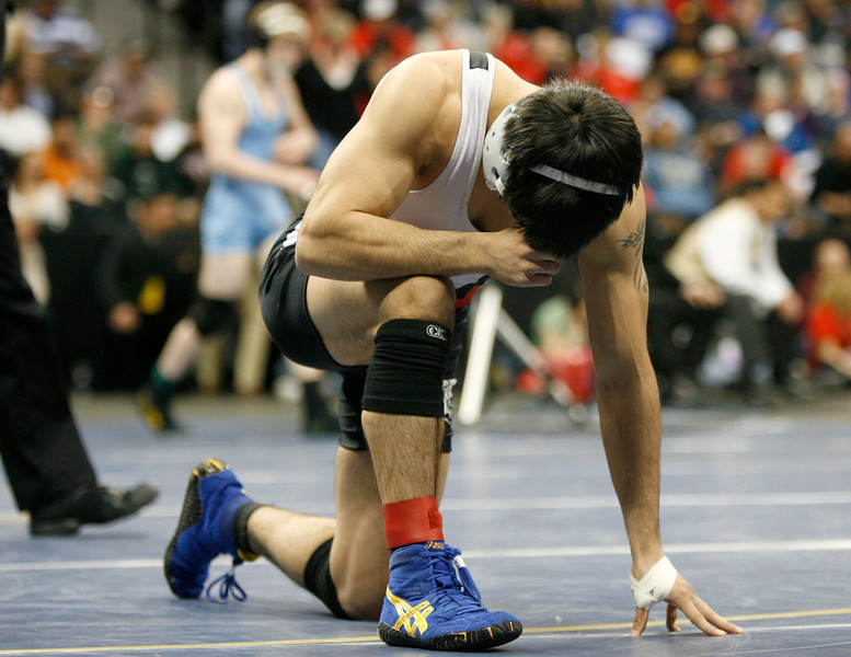 Loveland High School senior, Garrett Vasquez says a prayer before wrestling Mountain Range High School junior, Cory Mitze during the 5A 140 lb. Colorado State Wrestling finals on Saturday at the Pepsi Center in Denver. (Photo by Gabriel Christus)