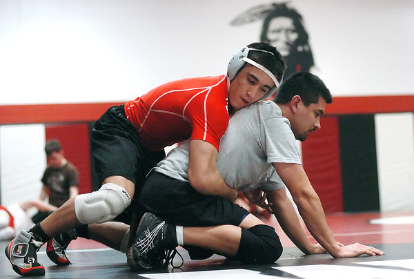 Loveland High School wrestler Garrett Vasquez, top, works on a drill with assistant wrestling coach Lorezo Dominguez during practice Tuesday, Jan. 12, 2010 in the school's wrestling room.