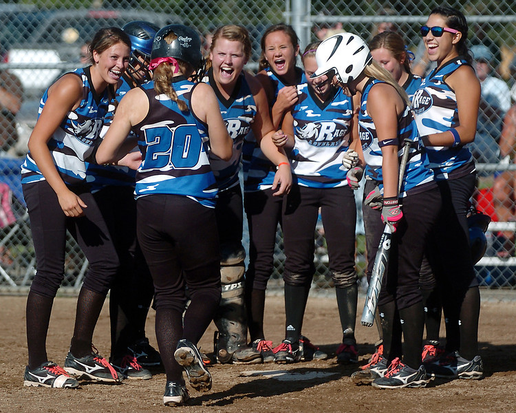 Loveland Rage 16A player Addie Coldiron (20) is congratulated by teammates at home plate after hitting a home run in the bottom of the second inning of their game against the Northern Colorado Roadrunners on Friday at the Barnes Softball Complex. The Rage won, 4-2.