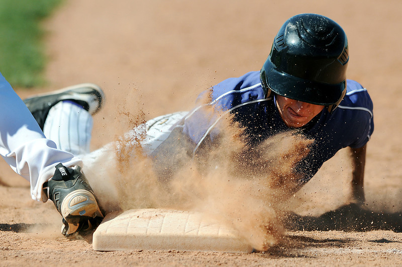 30 of Johnson's Corner slides safely back to first base before 7 of Broomfield can tag him out in the bottom of the 5th inning of Thursday afternoon's game at Mountian View High School. Johnson's Corner won the game 12-8.