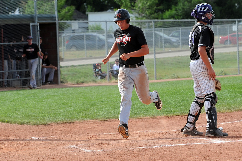 Legion Post 70's Nate Trobee steps on home plate to score a run behind Johnson's Corner catcher Dakotah Shea-Shelley in the top of the third inning of their game at Brock Field on Wednesday, July 18, 2012.