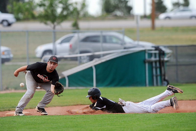 Johnson's Corner baserunner Adam Baumann slides safely into third base for a steal before the tag attempt by Legion Post 70's Jaxon Davenport in the bottom of the fifth inning of their game at Brock Field on Wednesday, July 19, 2012.