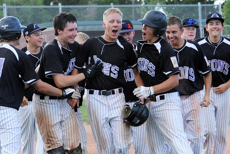 Kollin Evens, middle, is congratulated by his Johnson's Corner teammates after hitting a walk-off home run to defeat Davidson Chevrolet, 2-1, at Brock Field on Tuesday, July 17, 2012.