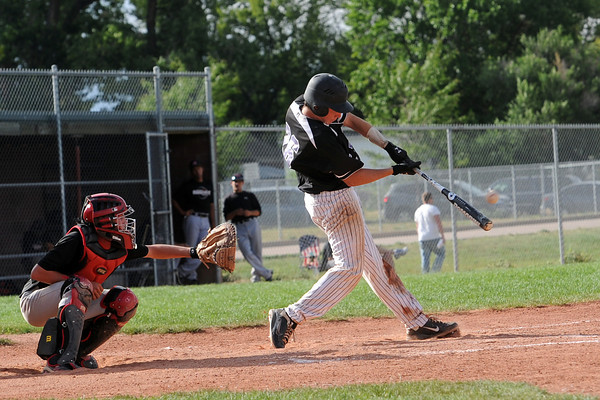 Johnson's Corner's Dakotah Shea-Shelley hits a home run in front of Legion Post 70 catcher Austin Olson in the bottom of the third inning of their game at Brock Field on Wednesday, July 18, 2012.