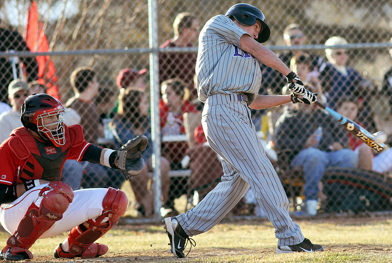 Loveland High School catcher Darryl Baca watches as Mountain View's Joey Hlushak smacks a triple in the top of the fifth inning of their game on Friday, March 12, 2010 at Swift Field. Mountain View won in the sixth inning, 13-3.