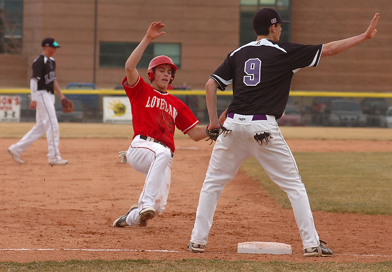 Loveland High School baseball player #5 slides into third base Monday as Mountain View's #9 waits for the ball during their game at MVHS.