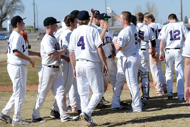 Mountain View High School's Justin Clinton (9) is congratulated by teammates after driving in the winning run in the bottom of the ninth inning of a game against Greeley Central on Saturday, March 10, 2012 at MVHS.