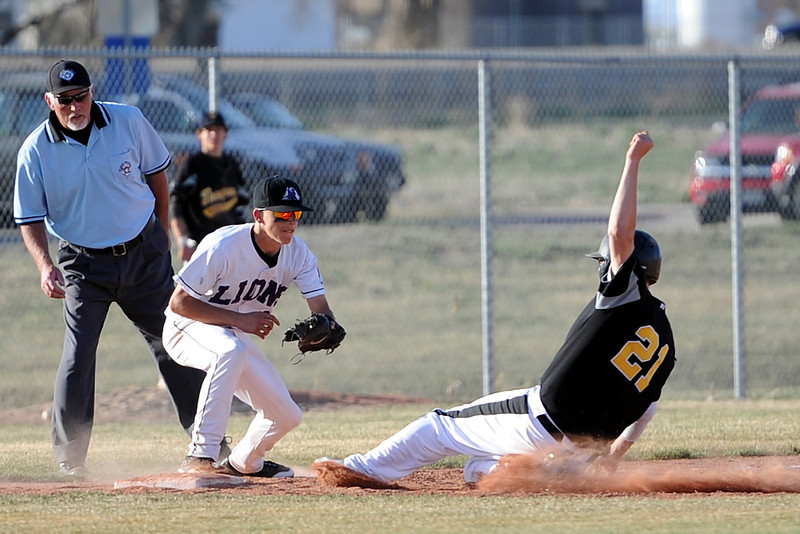 Thompson Valley High School baserunner Zack Wynn slides safely into third base in front of Mountain View's Adam Baumann after advancing on a fly ball in the top of the sixth inning of their game Thursday, March 29, 2012 at Brock Field.