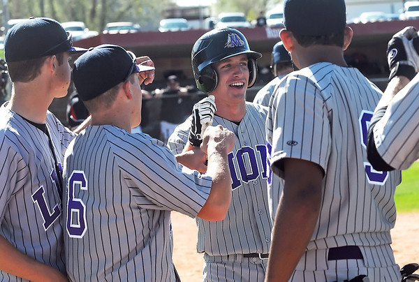Mountain View High School junior Joey Hlushak, center, is congratulated by temmates after hitting a home run in the top of the second of a game against Roosevelt on Tuesday at RoughRider Ballpark in Johnstown. The Mountain Lions won in five innings, 15-1.