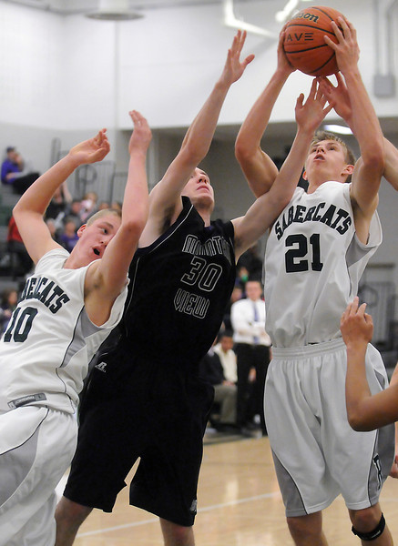 Mountain View High School senior Spencer Stetler (30) goes up for a rebound between Fossil Ridge's Alec Quaid (10) and Brett Baeverstad (21) in the fourth quarter of their game on Saturday, Dec. 4, 2010 at FRHS.