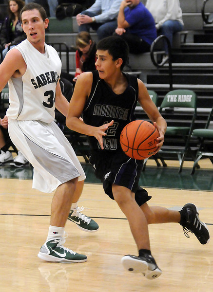 Mountain View High School junior Armando Garcia drives the baseline around Fossil Ridge's Alex Blum in the third quarter of their game on Saturday, Dec. 4, 2010 at FRHS.