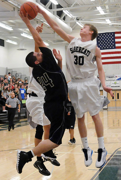 Mountain View High School junior Osman Orrantia (24) has his shot blocked by Fossil Ridge's Colin Peter (30) in the fourth quarter of their game on Saturday, Dec. 4, 2010 at FRHS.
