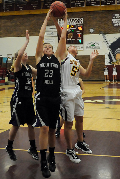 Mountain View High School's Rikelle Berry (23) goes up for a rebound between teammate Kaitlin Miller (32) and Berthoud's Amy Loberg in the fourth quarter of their game on Tuesday, Dec. 7, 2010 at BHS. Mountain View won, 46-27.