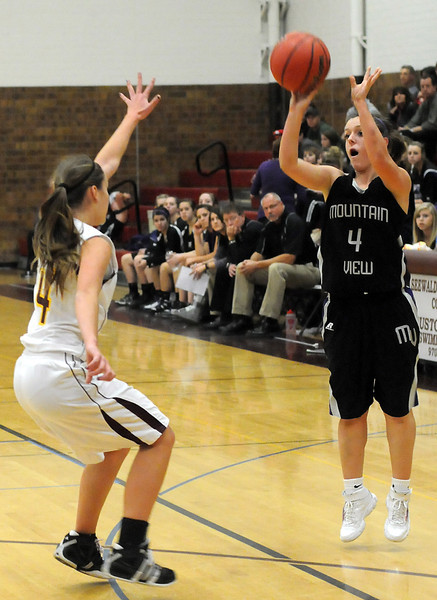 Mountain View High School's Kelli Hlushak, right, takes a shot over Berthoud's Dillon Fagler in the first quarter of their game on Tuesday, Dec. 7, 2010 at BHS.