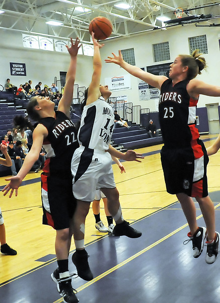 Mountain View High School freshman Andrea Baumann goes up for a rebound between Roosevelt's Tiffany Trimble, left, and Kaitlin Flynn in the second quarter of their game on Friday, Feb. 5, 2010 at MVHS.