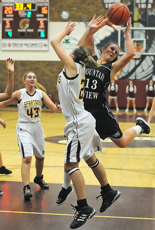 Mountain View High School junior Kellie Eastman battles for a rebound with Berthoud's Kacey Fagler as Sarah Loberg looks on in the second quarter of their game on Thursday, Feb. 11, 2010 at BHS. The Mountain Lions won in overtime, 41-35.