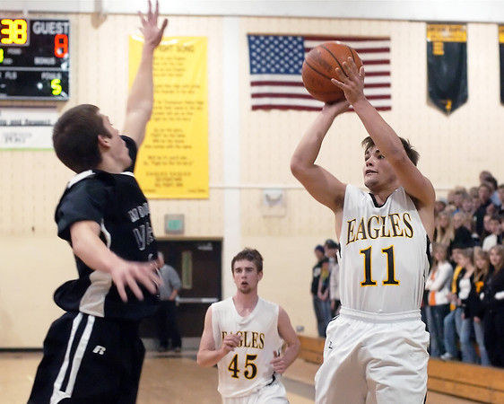 Thompson Valley High School's Jordan Carroll takes a shot over Mountain View's Brennan Stine as Andrew Pomerleau looks on in the first quarter of their game Friday night at TVHS.