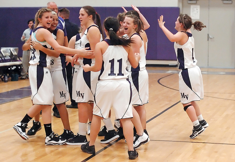 Members of Mountain View High School's girls basketball team celebrate their victory over Thompson Valley at the conclusion of their game Friday night at MVHS. The Mountain Lions won, 49-47.