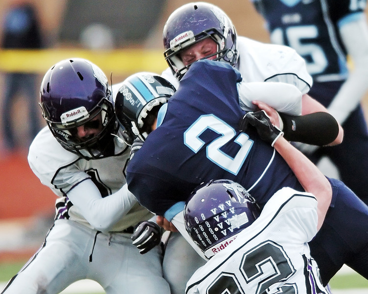 Mountain View High School defenders Keeton Krause, left, Jesse Tyrrell, back, and Joey Hlushak combine to tackle Valor's Ryan Nu'u during the third quarter of their semi-final game of the Class 3A State Football game on Saturday at Valor Stadium in Highlands Ranch. The Mountain Lions lost, 21-14.