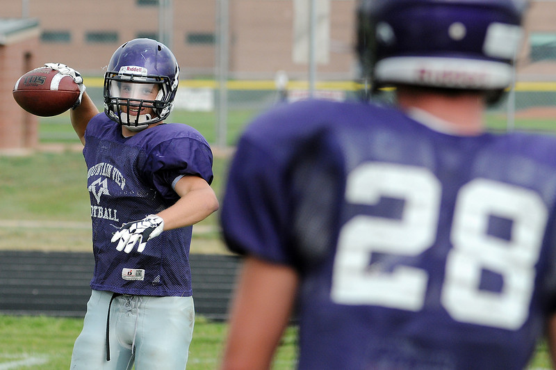 Steve Ryan, left, tosses Joey Hlushak a ball during football practice on Monday at Mountain View High School.