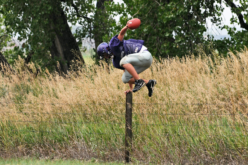 Joey Hlushak vaults a fence after retrieving an errant football during football practice Monday at Mountain View High School.