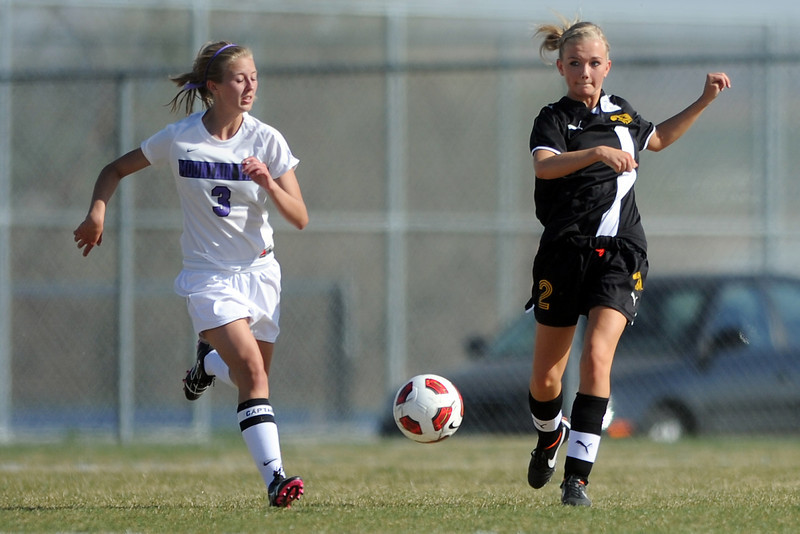 Thompson Valley High School's Tori Briggs, right, passes the ball in front of Mountain View's Sarah Ross in the first half of their game Tuesday, April 10, 2012 at MVHS.