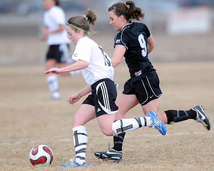 Loveland High School sophomore Kiara Gogarty, left, and Mountain View junior Kayla Grimes track down the ball in the first half of their game on Friday, March 5, 2010 at MVHS. Loveland won, 4-1.