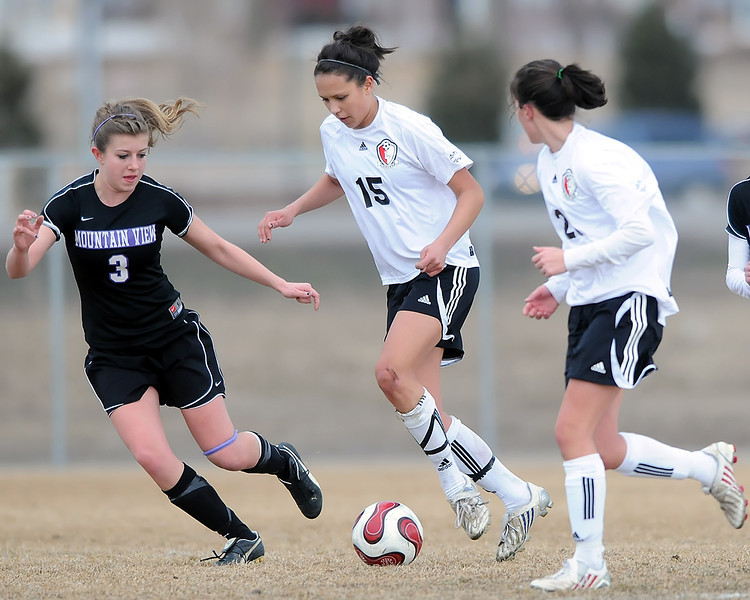 Loveland High School junior Moli Keeler, center, brings the ball up against Mountain View's Rikelle Berry while Katrina Bossenbroek looks on in the first half of their game on Friday, March 5, 2010 at MVHS. Keeler scored two goals in the Indians' 4-1 win over the Mountain Lions.