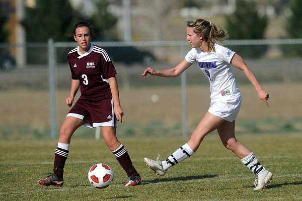 Mountain View High School's Kristen Barkman, right, passes the ball in front of Berthoud defender Emma Otto in the first half of their game Wednesday, March 28, 2012 at MVHS.