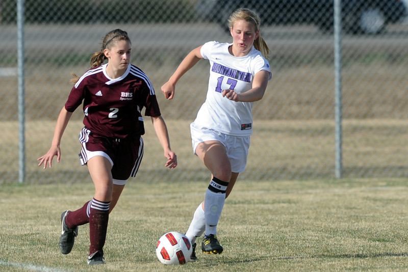 Berthoud High School's Sara Sterck, left, and Mountain View's Abbey Metzger race down the sideline in the second half of their game Wednesday, March 28, 2012 at MVHS.