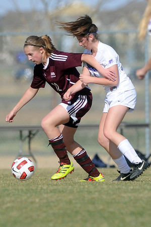 Berthoud High School junior Lindsey Loberg, left, and Mountain View's Hallie Stolte track down the ball in the first half of their game Wednesday, March 28, 2012 at MVHS.