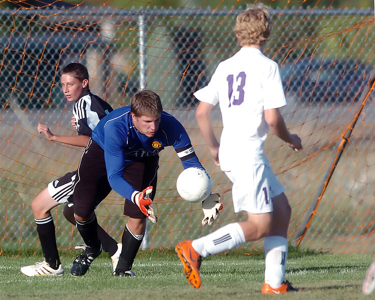 Mountain View High School goalie Quinn Benson makes a stop while teammate Kevin Bell, right, and Roosevelt's Logan Dingwall look on in the second half of their game on Thursday, Sept. 30, 2010 at MVHS. The Mountain Lions won, 7-0.