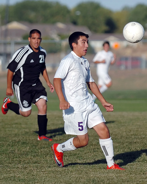 Mountain View High School senior Tony Fabian (5) tracks down the ball in front of Roosevelt's Omar Portillo in the second half of their game on Thursday, Sept. 30, 2010 at MVHS. The Mountain Lions won, 7-0.
