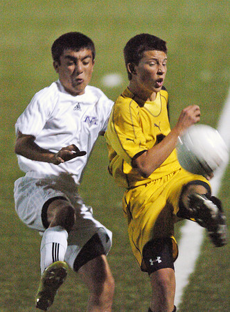 Mountain View High School's Tony Fabian, left, and Thompson Valley's Seth Rickard track down the ball in the first half of their game Monday night at the Loveland Sports Park. Mountian View won, 1-0.