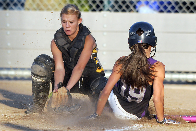 Mountain View High School freshman Andrea Baumann, right, slides safely home as Thompson Valley High School catcher Ashley Browning loses track of the ball during the top of the 8th inning. Mountain View won the game 7-3.