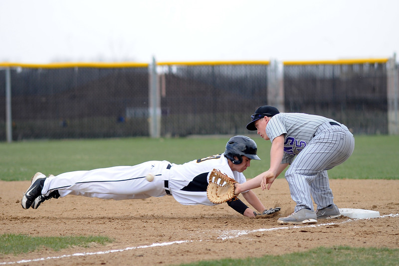 Thompson Valley High School baserunner Jesse Shaw dives back to first base ahead of the tag by Mountain View first baseman Ozzie Pearcy on a pickoff attempt in the bottom of the second inning of their game Thursday, April 26, 2013 at Constantz Field.