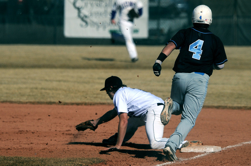 Mountain View junior Hunter Porterfield snags a low thrown ball at first base to get the out on Greeley West senior Nate Loera during the first inning of a game played Monday afternoon at MVHS.