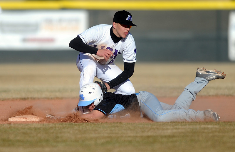Mountain View High School sophomore Adam Baumann, left, tags out Greeley West senior Nate Loera during the forth inning of a game played Monday evening at MVHS.