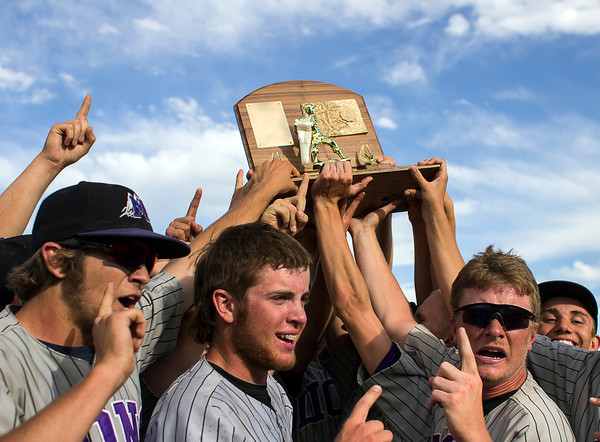 Mountain View High School baseball players hold up the Colorado State High School 4A championship trophy after a game played against Pueblo West on May 25, 2013, in Denver, Colo. (Photo by Timothy Hurst)