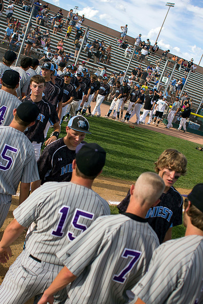 Mountain View High School baseball players (gray jerseys) line up to shake hands with Pueblo West High School baseball players after a win by Mountain View at the Colorado State High School 4A Championship game, May 25, 2013, in Denver, Colo.(Photo by Timothy Hurst)