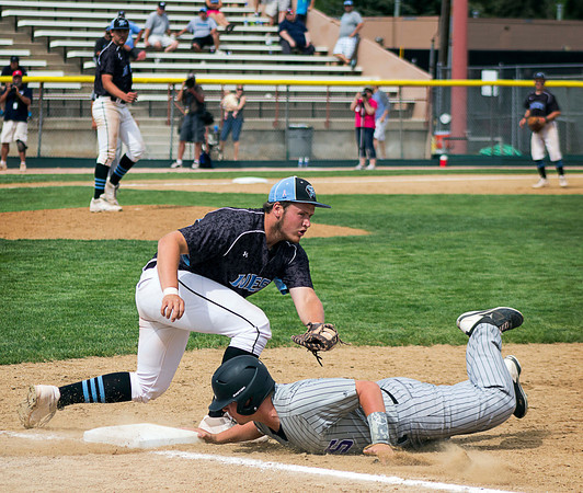 Mountain View's Justin Clinton, right, gets back to first safe after an  attempted tag-out by Pueblo West's Gavin Compton in the third inning of the Colorado State High School 4A Championship game, May 25, 2013, in Denver, Colo. (Photo by Timothy Hurst)