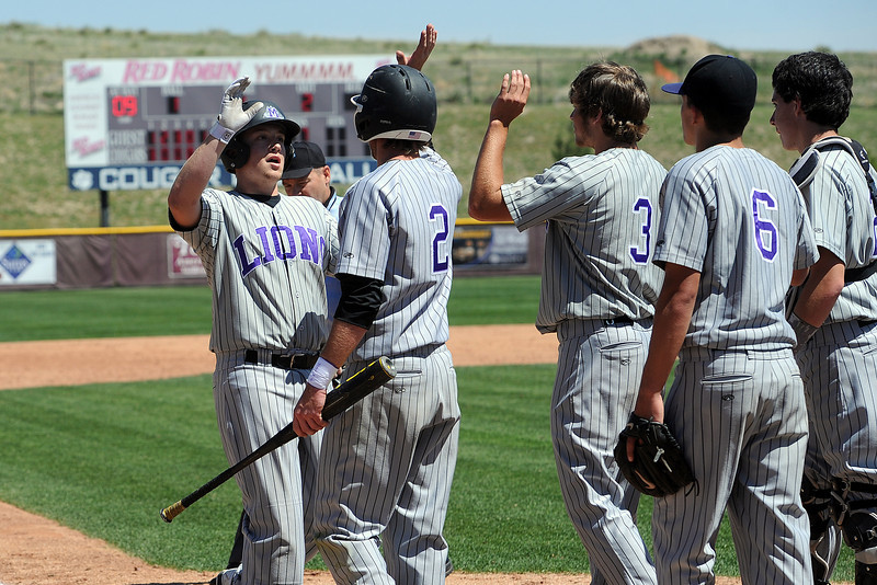 Mountain View High School's Justin Clinton, left, is congratulated by teammates at home plate after hitting a home run in the top of the fifth inning of a game against Windsor on Friday, May 17, 2013 at Cherokee Trail High School in Aurora, Colo.