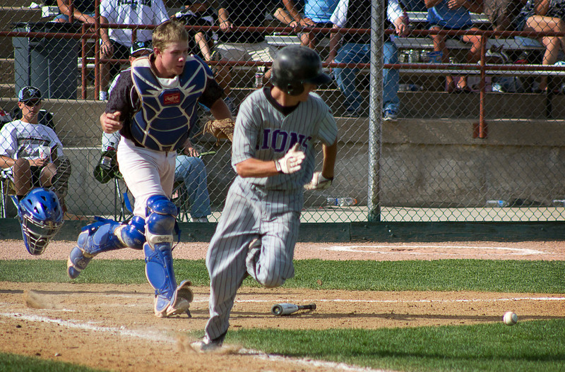 Pueblo West's Dustin Peterson, left, chases down a sacrifice-bunt by Mountain View's Justin Dennis in the eighth inning of the Colorado State High School 4A Championship game, May 25, 2013, in Denver, Colo. Dennis would be called out at first, but his bunt helped put Mountain View in position to score the eventual game-winning piont. (Photo by Timothy Hurst)