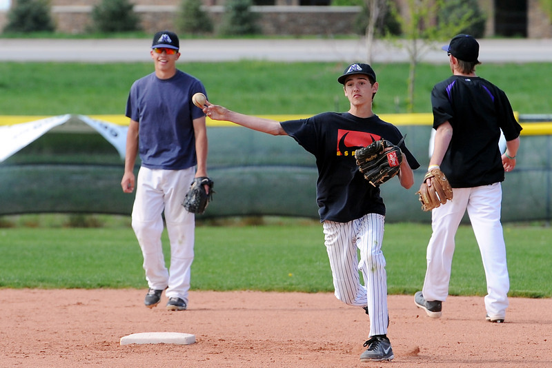 Mountain View High School's Locke Bernhardt, middle, throws to first base while working on a drill with teammates Adam Baumann, left, and Max Moree during practice Tuesday, May 21, 2013 at MVHS.