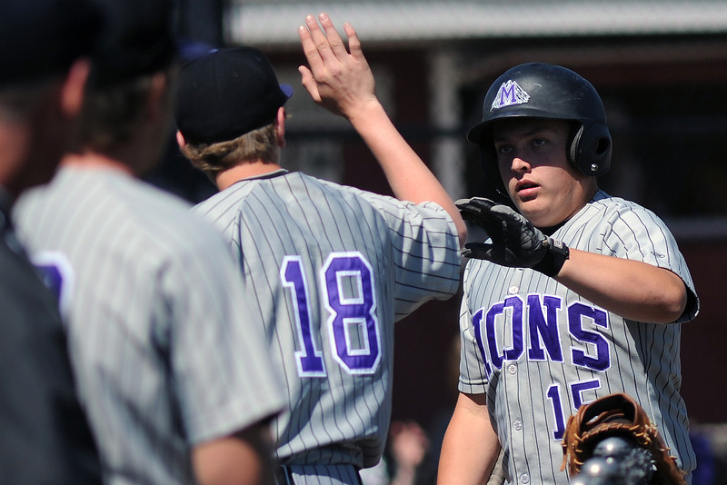 Mountain View High School sophomore Ozzie Pearcy, right, is congratulated by teammate Chad Riggenbach (18) after scoring a run in the top of the second inning of a game against Windsor on Friday, May 17, 2013 at Cherokee Trail High School in Aurora, Colo.