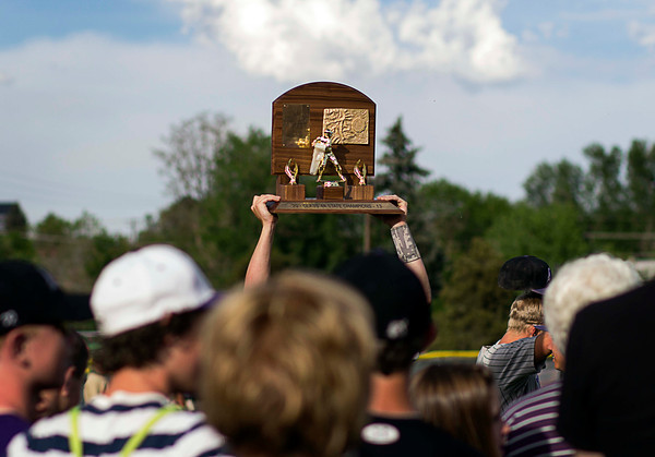 A Mountain View baseball player hoists the Colorado State High School 4A Championship trophy above a gathering crowd after an overtime win against number-one seeded Pueblo West, May 25, 2013, in Denver, Colo. (Photo by Timothy Hurst)